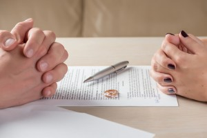 Couple's Hands Signing Papers to Update Estate Plan