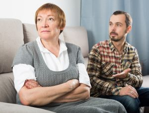 Older Mother on Couch Considers Disinheriting Son