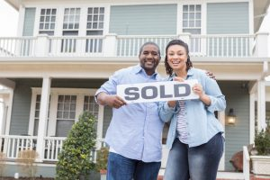 Couple Holding SOLD Sign in Front of House