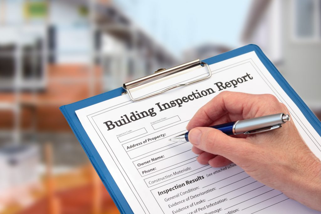Building Inspector completing an inspection form on clipboard beside new build construction