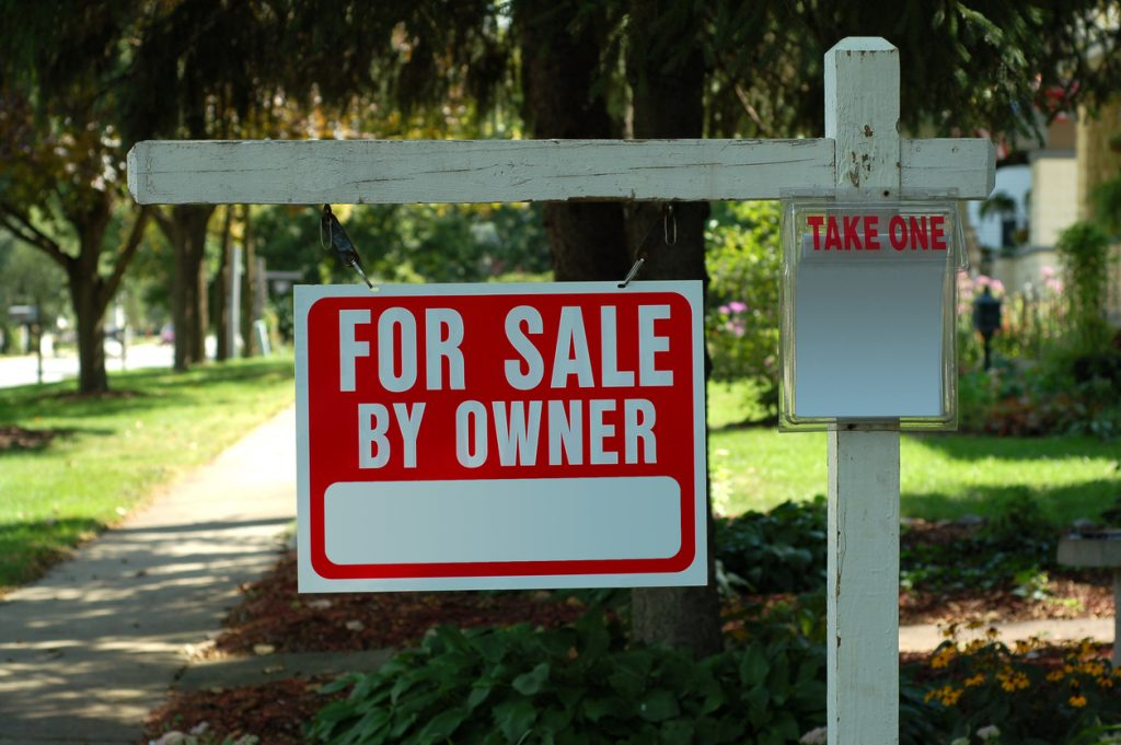 Home for sale by owner real estate sign hanging from a wooden post in the front yard.